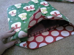 Next, use your thumb to tuck in the center pieces of the outside edges of the wrapping paper.  There is Monsieur le Snowhomme sneaking into the photo on my thumbnail.