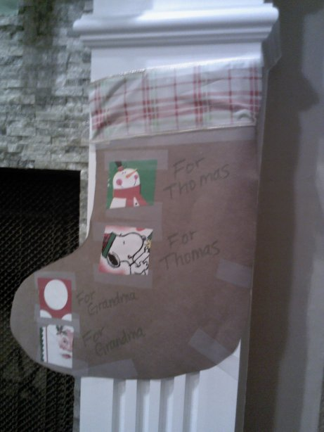 I decided to make a Gift Guide for my present openers.  Using scraps from my wrapping paper, I cut out little squares and taped them to a stocking cut-out.  I wrote the names of the people whose gifts were wrapped in that paper next to each scrap.  The more in your family, the merrier this will make you when it is time to open the gifts.